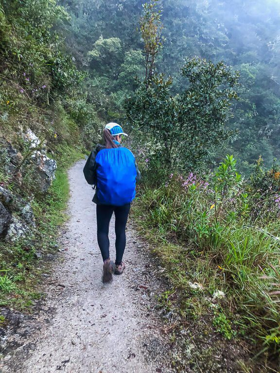 Kristen wearing backpack and cover walking on trail in Peru