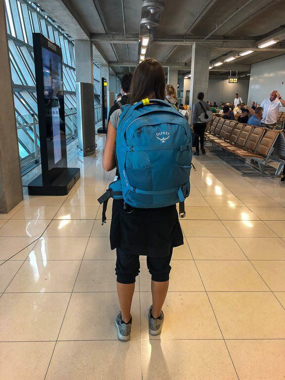 Kristen wearing her osprey farpoint 40 in airport terminal compact and lightweight backpack