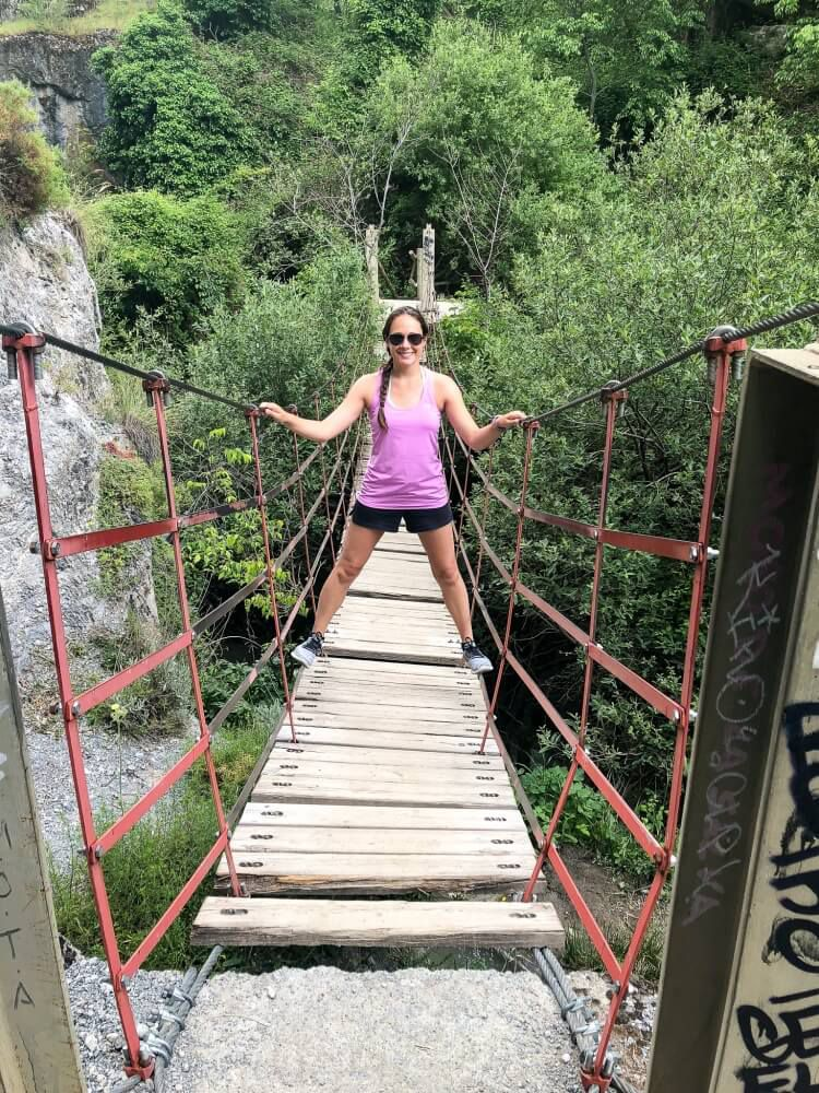 Kristen standing on hanging bridge on los cahorros hiking trail