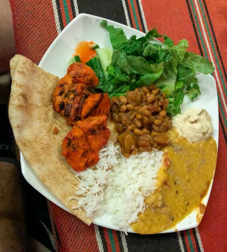 A curry, beans, salad and rice during a desert dinner