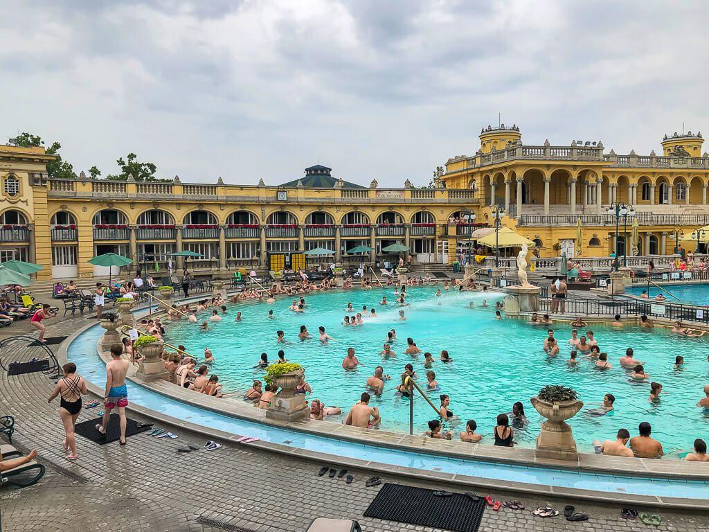tourists enjoying szechenyi thermal baths outdoor pool
