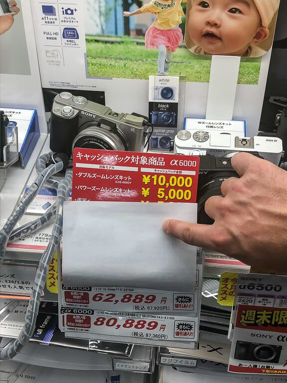 Mark holding paper up to reveal price of camera in a tokyo store