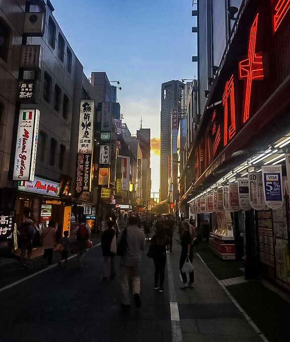 Tokyo street at sunset with lights on buildings