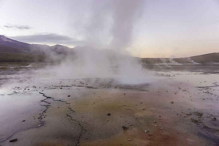post sunrise geyser field with range of colors on ground near smoke bellowing