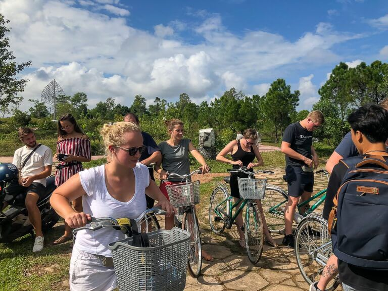 group of backpackers on bikes paying guide into abandoned water park hue