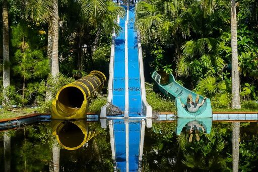 mark pretending to slide into a pool on a green water slide