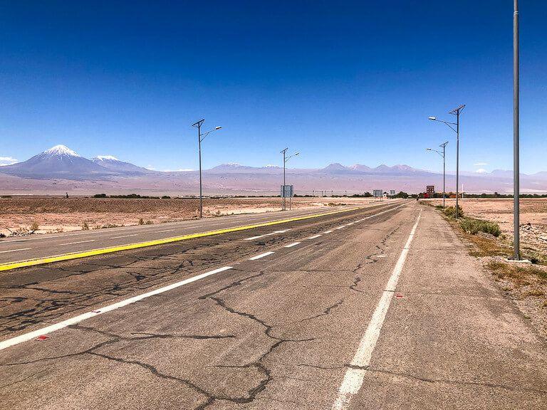 open road with volcanoes in background near San Pedro de atacama town