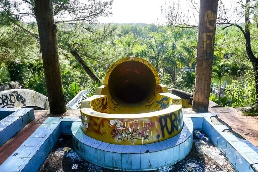 Entrance to yellow tube slide at water park in hue