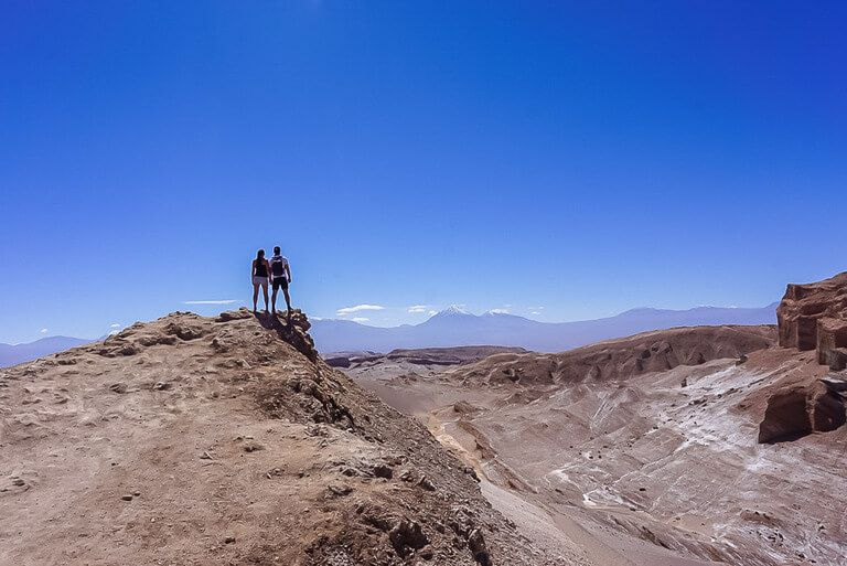 Mark and Kristen stood on edge of rock with amazing view of Valle de la luna and volcano