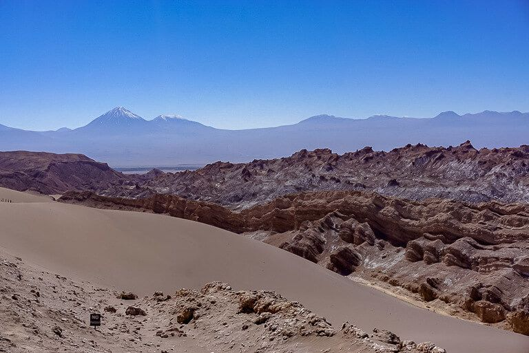 spectacular views of sand dune and jagged red rocks in valle de la luna