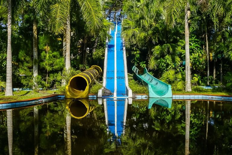 Abandoned water park hue Colorful water slides reflecting in pool below