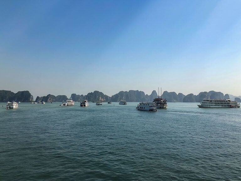 loads of cheap Halong Bay cruise boats sailing into limestone rocks