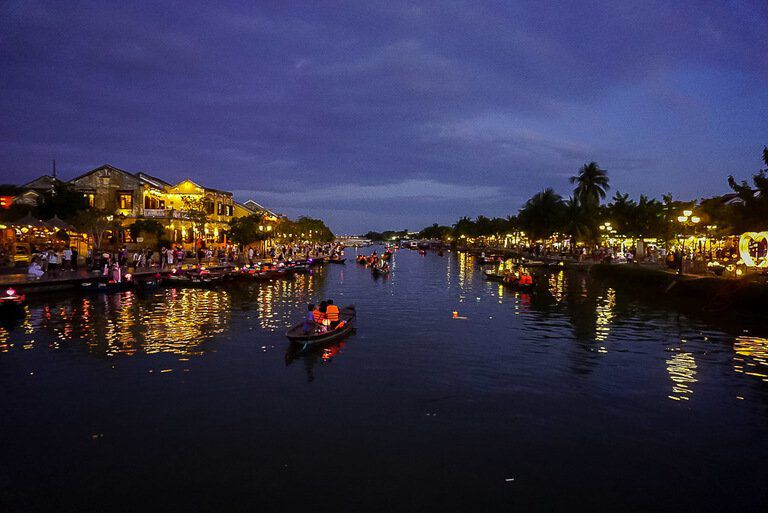 Boats on Thu Bon River in Hoi An Vietnam at night building lit up