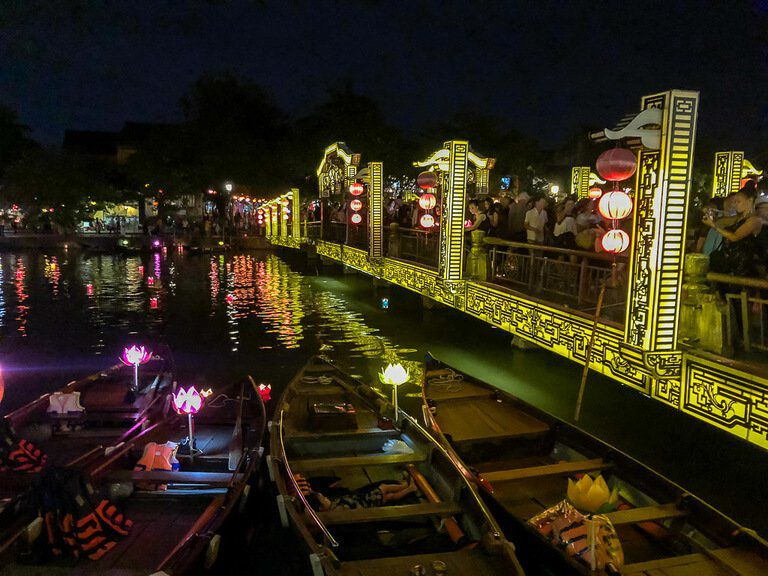 boats on bank of river next to bridge of lights in Hoi An vietnam at night