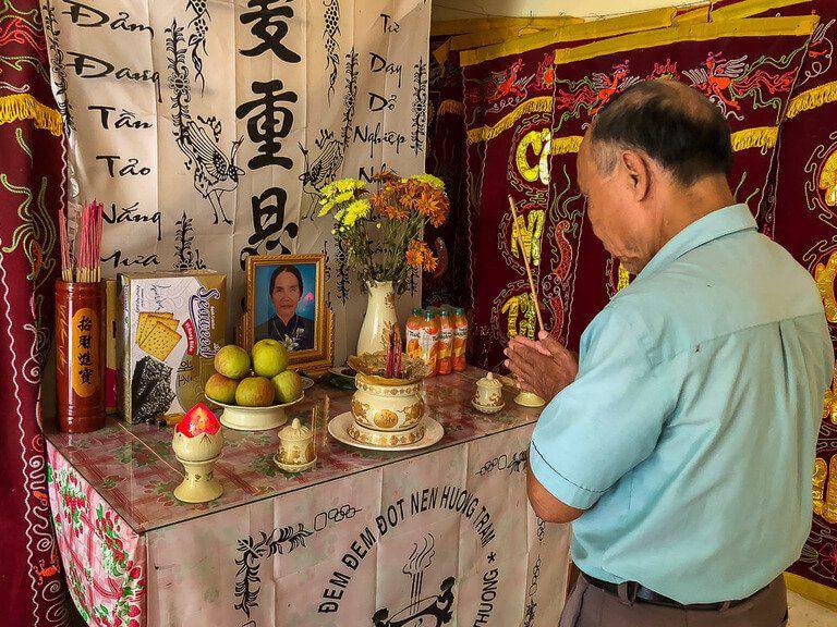 Vietnamese man praying to shrine in his home