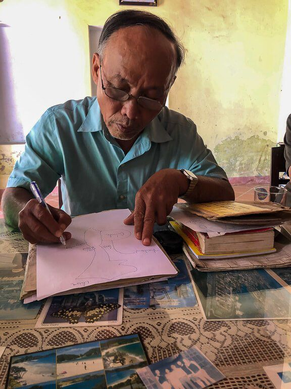 Vietnamese man writing on pink paper in his house private Hoi An tour