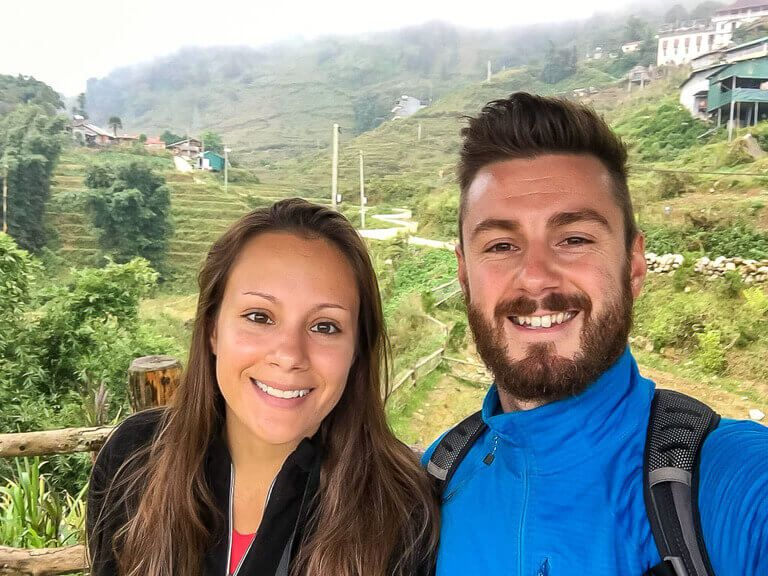 Mark and Kristen in sapa vietnam with rice terraces behind 2 day itinerary