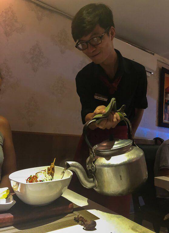 Waiter pouring water into Kristen's broth in Duong's restaurant Hanoi