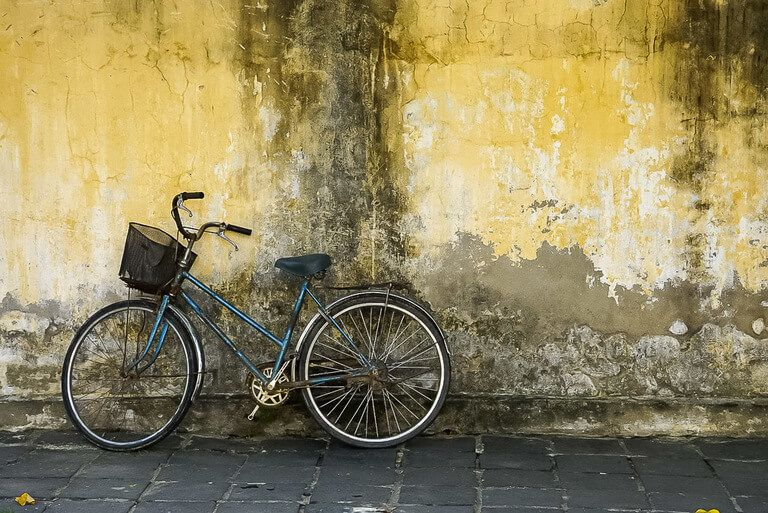 Blue bicycle leaning against yellow wall in Hoi An Vietnam How to get from da nang to Hoi An