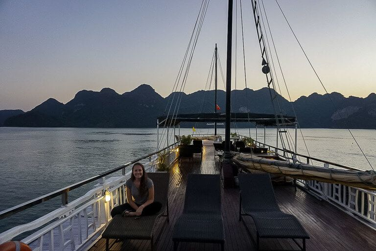 kristen sat on top deck of Rosa Cruise at dusk in Halong Bay