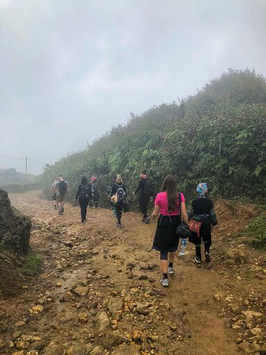 Kristen hiking along a dirt track in clouds sapa