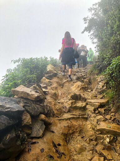 Kristen walking up rocky path in clouds sapa itinerary vietnam