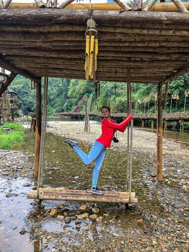 Kristen standing with one leg up on a wooden swing in Sapa Vietnam