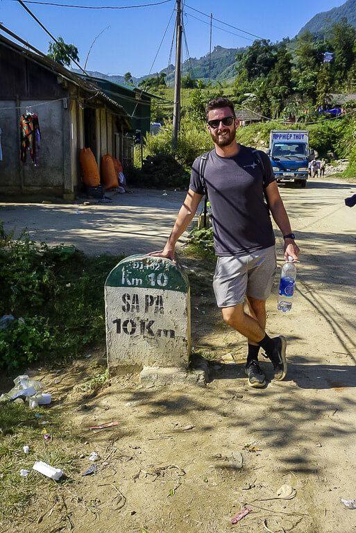Mark stood next to 10km sapa stone sign in sunshine