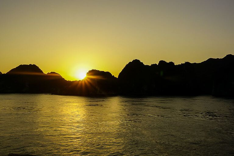 Sunset over limestone karsts in Halong Bay on a cheap cruise