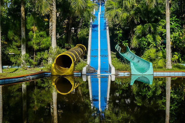 Colorful water slides reflecting in water in hue