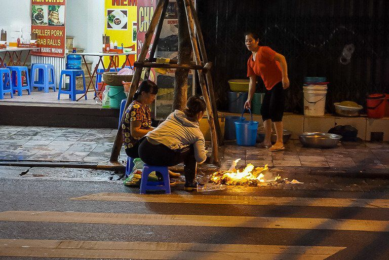 Women cooking food on street in Hanoi flames on ground