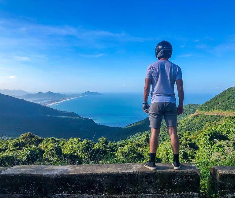 Mark with motorbike helmet on overlooking bay from top of hai van pass between hue and da nang Vietnam
