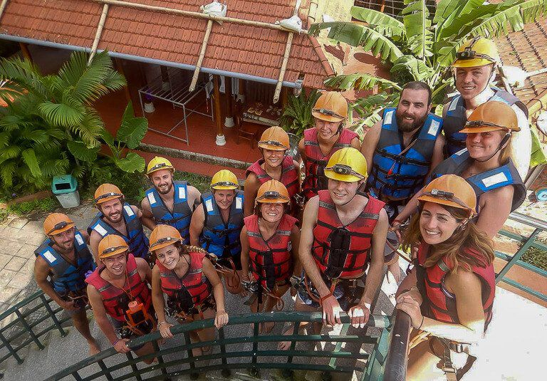 Tour group at Dark Cave Phong Nha on stairs before zipline in life jackets