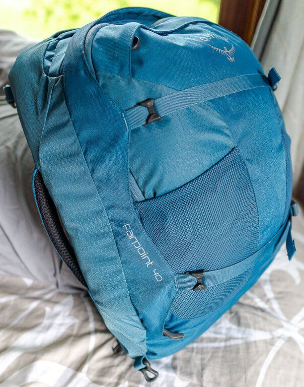 Front side view of blue Osprey Farpoint 40 backpack filled to show its capacity