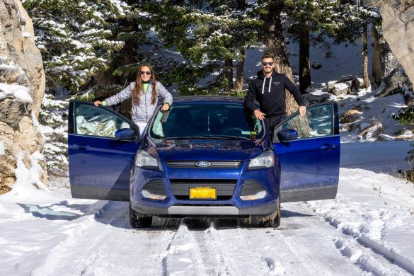 Mark Kristen with Blue Ford on snow in Yellowstone National Park road trip packing list