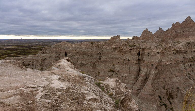 Mark on edge of rock face in badlands cloudy sky