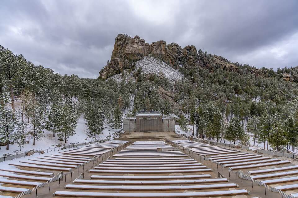 Empty amphitheater seating at mount rushmore national memorial in south dakota on a cloudy snowy day in april