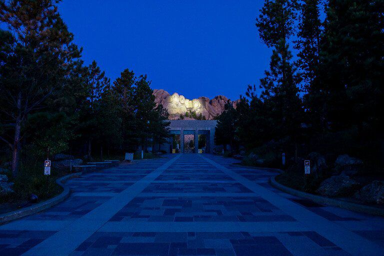 Approaching the entrance to Mount Rushmore with presidents heads small in distance