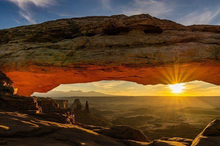 Mesa Arch sunrise glowing red with beautiful sunburst cutting through a hazy canyon floor
