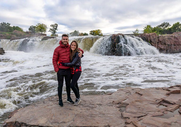 Mark and Kristen stood on rocks in front of Sioux Falls Park South Dakota