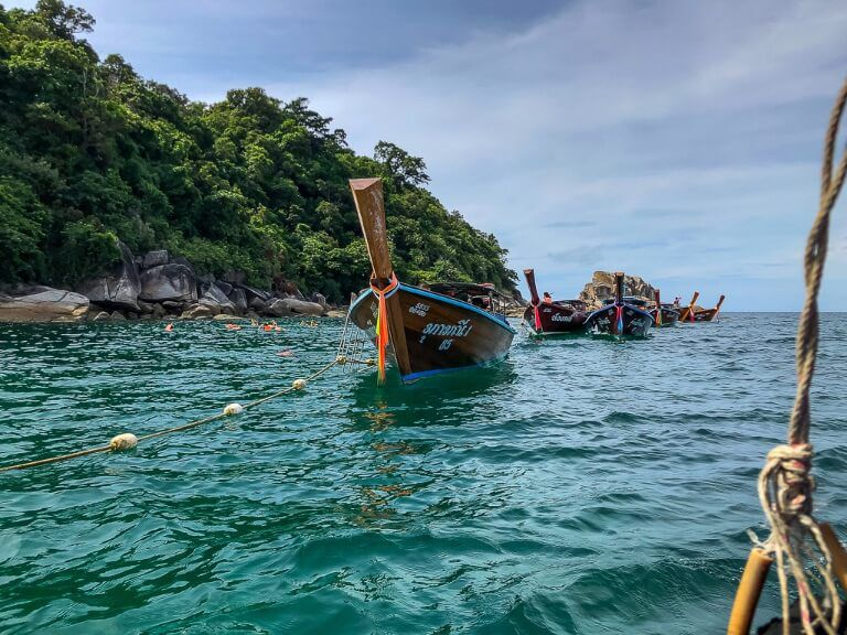 Long tail boats congregating around a snorkel site in Andaman sea