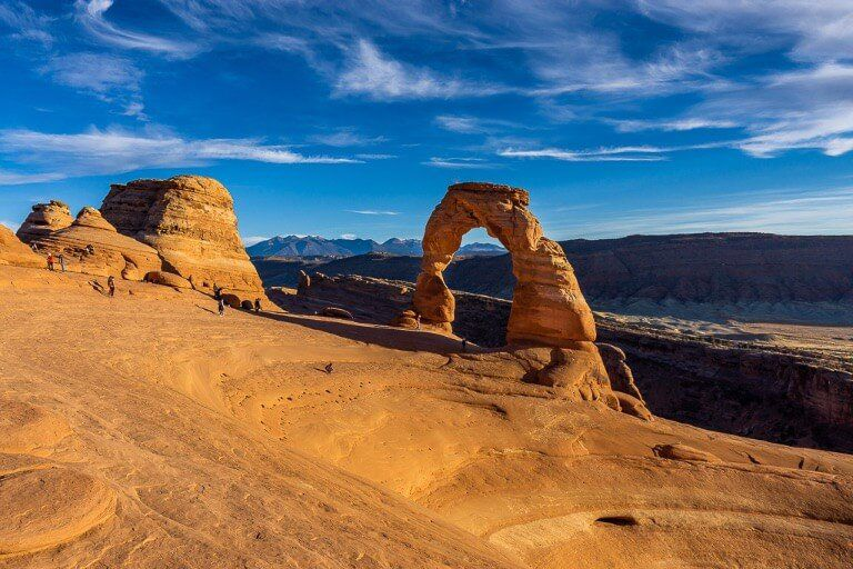 Delicate arch front view from summit of hiking trail photographers setting up to the left with deep bowl depression to the right