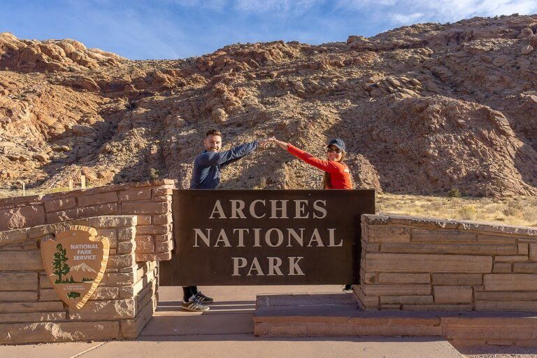 Mark and Kristen Where Are Those Morgans leaning into each other to create an arch above the Arches National Park entrance sign