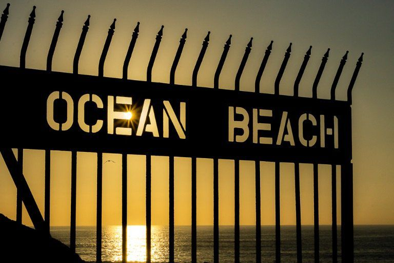 Ocean Beach sign with sunburst close to sunset in San Diego