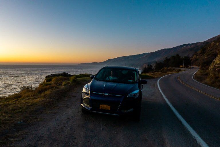 Our car parked on the side of California Pacific Coast highway 1 at sunset