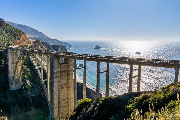 Bixby bridge is one of the most awesome attractions along California's Pacific Coast highway 1 road trip from san Francisco to San Diego beautiful bridge with Pacific Ocean backdrop and sun reflecting