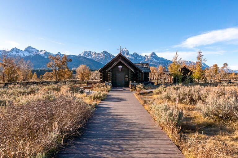 church of the transfiguration wooden boardwalk leading to church and surrounding mountains in grand teton national park wyoming