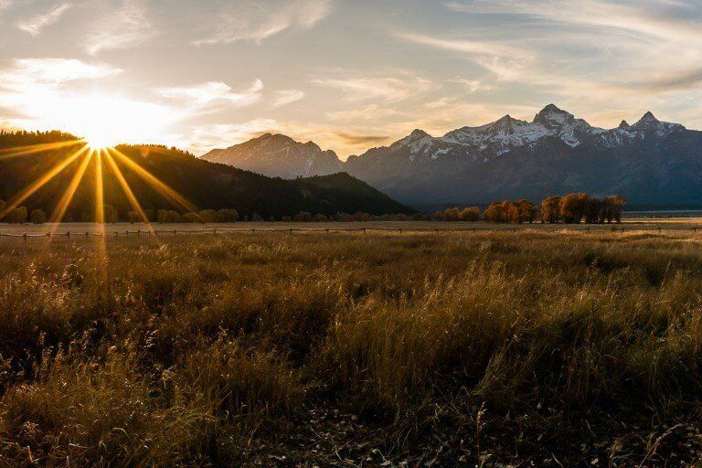 Beautiful starburst at sunset over hills and mountains in Fall