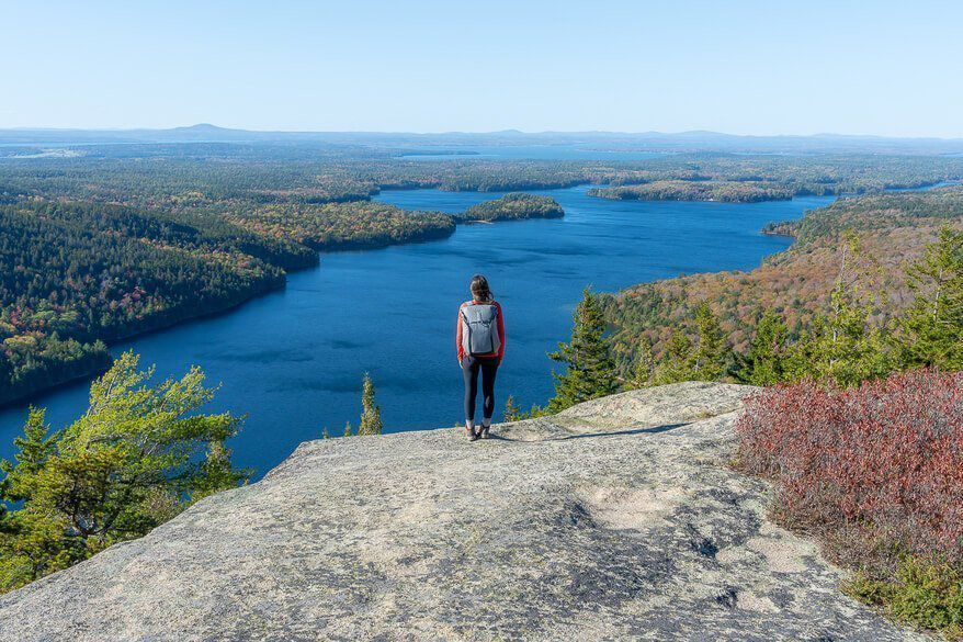 Kristen on a summit in Acadia National Park overlooking a huge lake with misty sky