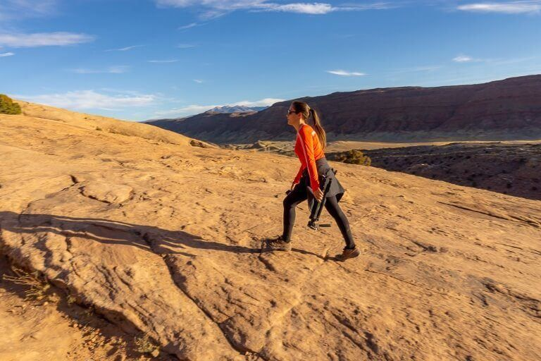 Kristen walking up a slab of rock to Delicate Arch in Utah for sunset